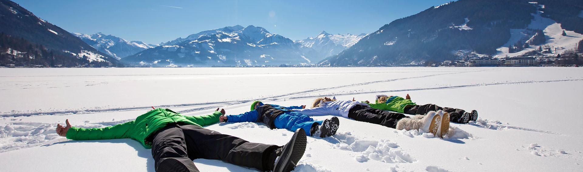 Familie liegt im Schnee bei perfektem Wetter